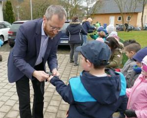 Bürgermeister Thiemig hilft den Kindern, die Handschuhe anzuziehen