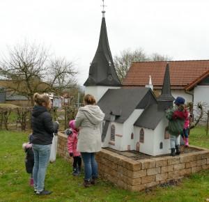 Kinder der Kita untersuchen ein Modell der Kirche Breidenbach