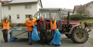 Die Müllsammler stehen vor einem Traktor mit Müllsäcken