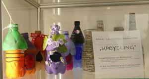 Vasen aus alten Glasflaschen und Vogelhäuschen aus Kunststoffflaschen in einer Glasvitrine