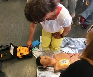 Frau bedient Defibrilator an einer Übungspuppe