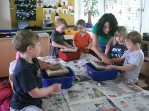 Schueler schoepfen Papier mithilfe von Frau Reichel