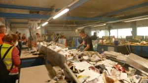 Verbandsmitglieder beobachten händische Papiersortierung am Laufband