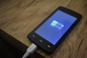 Ein Smartphone liegt auf einem Tisch und wird mit einem Kabel aufgeladen.