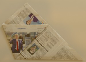 Falten Sie eine der spitzen Ecken an die gegenüberliegende Kante. Drehen Sie die Zeitung um und wiederholen diesen Vorgang mit der anderen Seite.