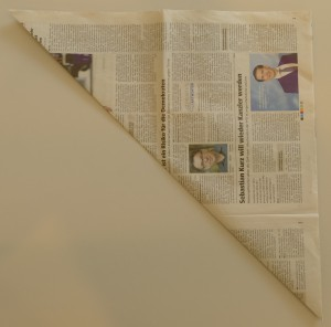 Falten Sie die linke untere Ecke der Zeitung genau auf die rechte obere Ecke - so entsteht ein Dreieck. Legen Sie das Dreieck anschließend so vor sich hin, dass die längste Seite nach unten zeigt bzw. in Ihrer Richtung liegt.