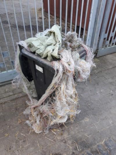 Landwirtschaftlich genutzte Folien sind in einer schwarzen Tonne entsorgt, die auf der Straße steht