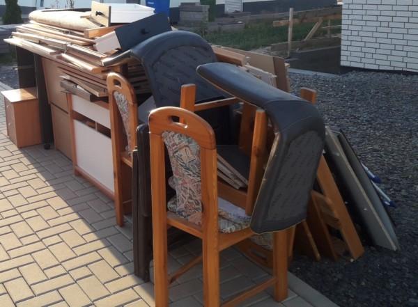 Das Bild zeigt einen ordentlich bereitgestellten Sperrmüll. Stühle und Schränke sind ineinandergestapelt.