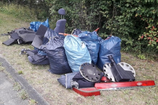 Am Straßenrand bereitgestellte Autoteile, in Tüten verpackter Müll.