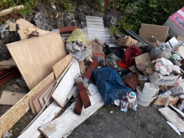 Ein ungeordneter Haufen mit Baumaterialien, Tüten und in Eimern verpackten Abfall.