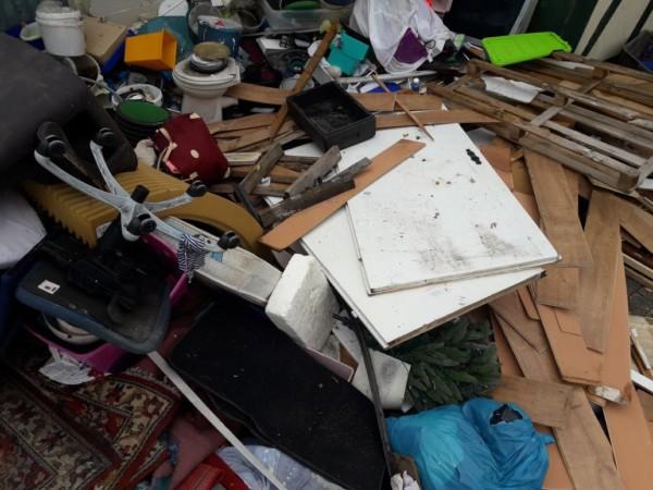 Das Bild zeigt einen ungeordneten Haufen aussortierter Haushaltsgegenstände und Müll in Tüten.