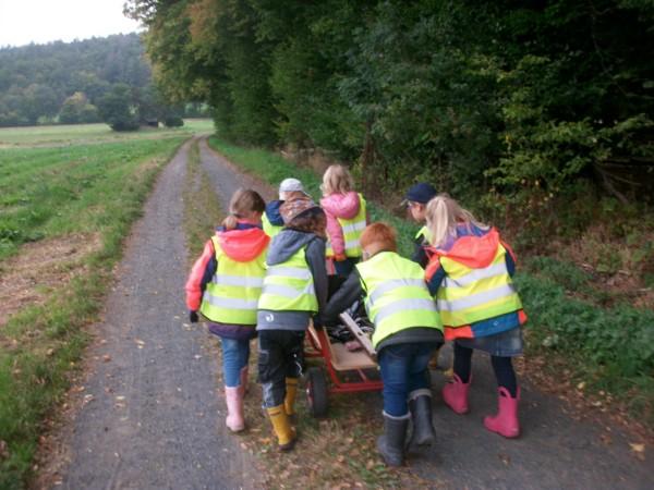 Kinder schieben einen Bollerwagen während der Müllsammel-Aktion.