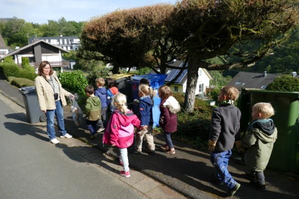 Frau Neumüller befragt die Kinder vor Mülltonnen zur Mülltrennung.