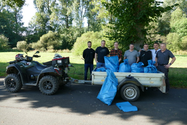 Biedenkopfer Sammelgruppe steht hinter einem Quad und mit blauen Säcken gefüllten Anhänger.