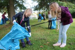 Zwei Schülerinnen sammeln mit Tüte und Zange Müll auf.